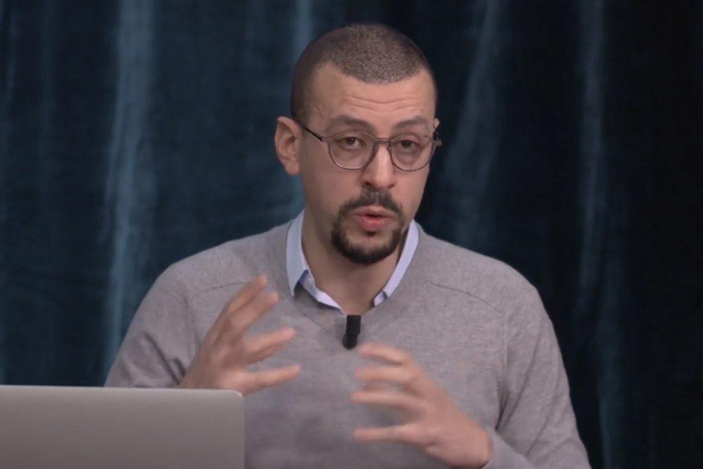 Mouloud Boukala, assis devant un ordinateur, donne des explications en s'exprimant avec ses mains